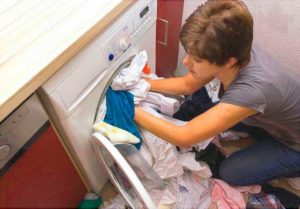 Загрузка контейнера барабана стиральной машины бельем