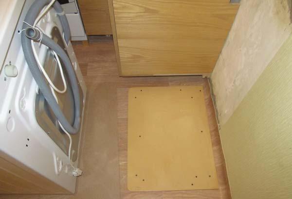 Выравнивание стиральной машины при помощи фанеры