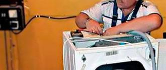 Мастер разбирает стиральную машину в ремонт